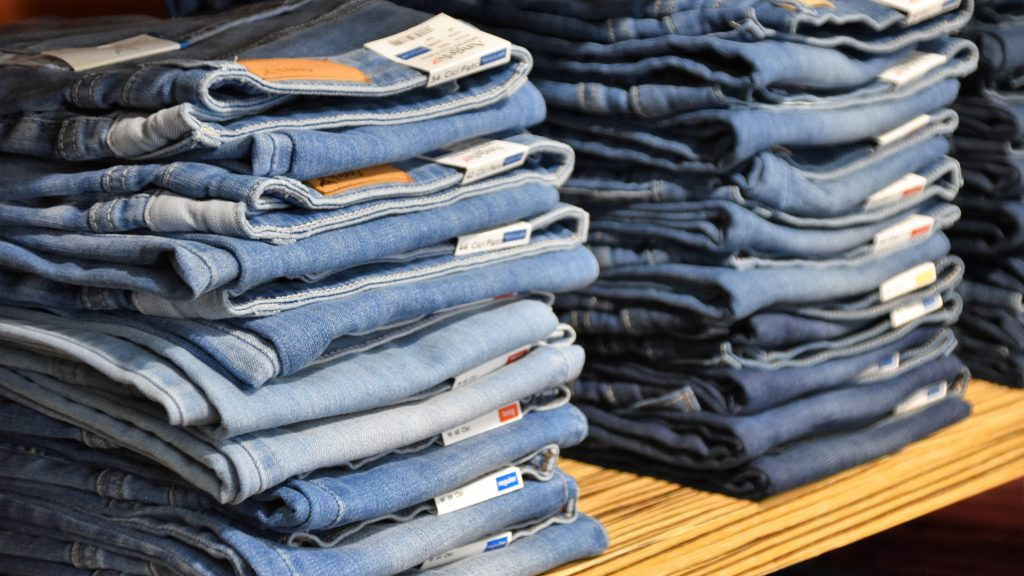 Exploring sustainable fashion on smoothmind. Pile of blue denim jeans lot